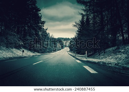 Asphalt road in winter landscape - stock photo