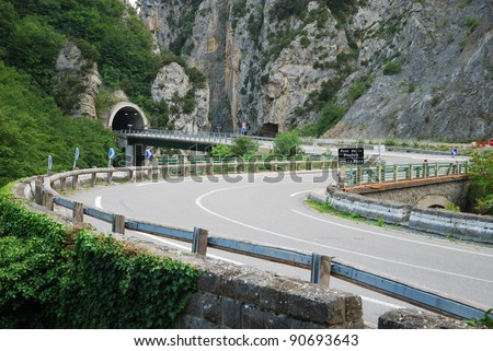 Asphalt road is twisting along sheer cliffs overgrown with lush greenery. Highway is winding through picturesque European Alps in summer. - stock photo