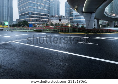 asphalt road leading into the city at night - stock photo