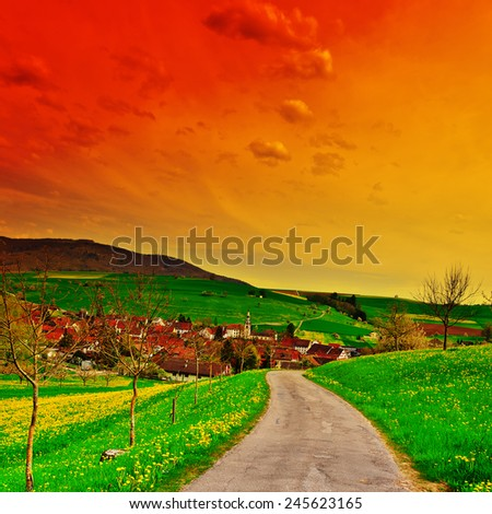 Asphalt Road Leading to the Small City in the Swiss Alps at Sunset - stock photo