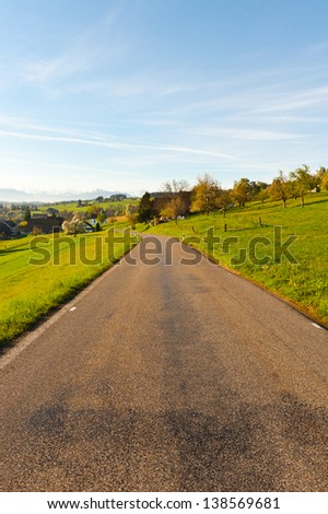 Asphalt Road Leading to the Small Swiss Town  in  Alps - stock photo