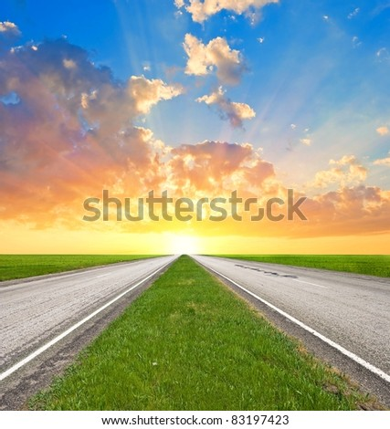 asphalt road leaving far to a sunset - stock photo