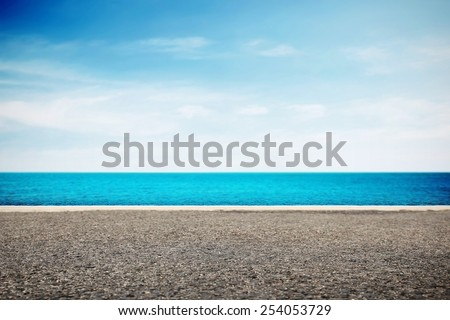 Asphalt road near water in summer - stock photo