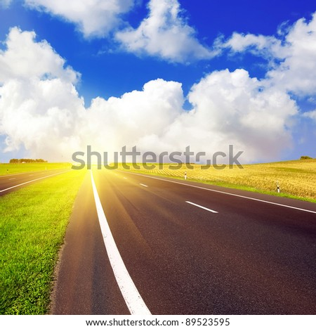 asphalt road over blue sky and sunrise or sunset - travel concept - stock photo