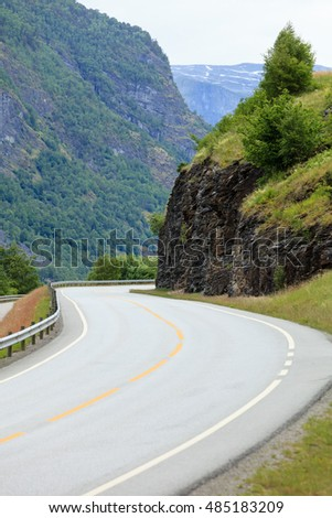 Asphalt road running through summer norwegian mountains. Travel and tourism.