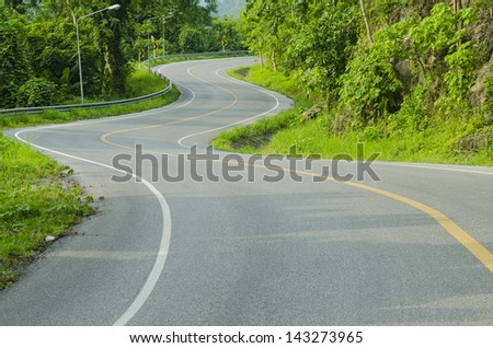 Asphalt road sharp curve along with tropical forest zigzag ahead. - stock photo