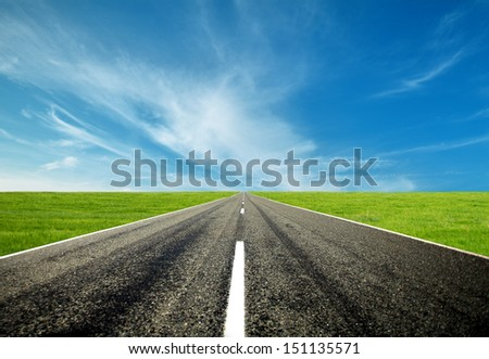 asphalt road straight through the green field with blue sky and cloud in summer - stock photo