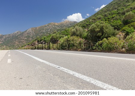 asphalt road stretches diagonally near the mountains - stock photo
