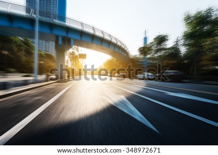 asphalt road through bridge to modern buildings at sunrise