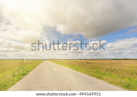 Asphalt road through the field with green grass under blue sky with clouds