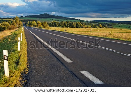 Asphalt road through the fields towards the horizon, wooded mountain on the horizon, dark stormy clouds - stock photo
