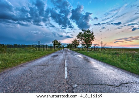 asphalt road through the green field and clouds on blue sky in spring day  - stock photo