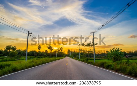 asphalt road through the green field on twilight sunset. - stock photo