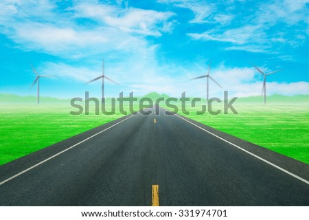 asphalt road through the green field with wind turbine and blue sky background