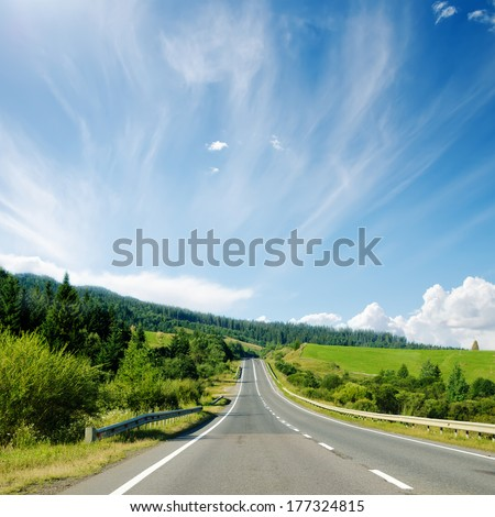asphalt road to horizon in mountain and blue sky - stock photo
