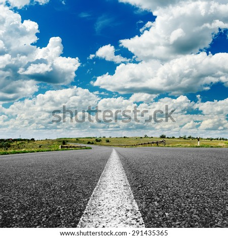 asphalt road to horizon under cloudy sky - stock photo