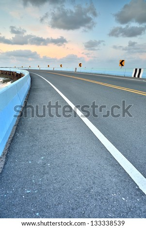 asphalt road to vertical in cloudy sky - stock photo