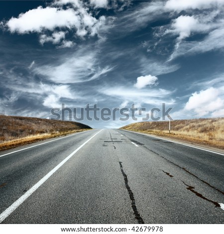 Asphalt road under fluffy clouds - stock photo