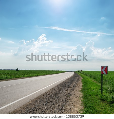 asphalt road under sun in sky - stock photo