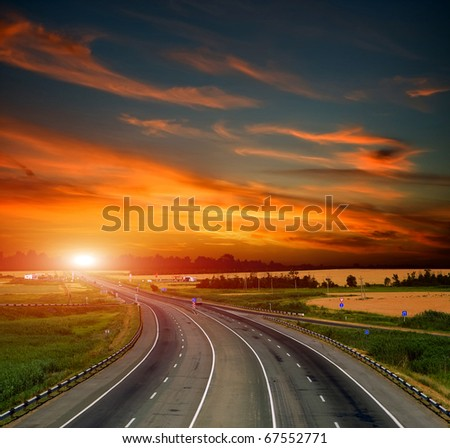 Asphalt road with a fence against the blue sky - stock photo