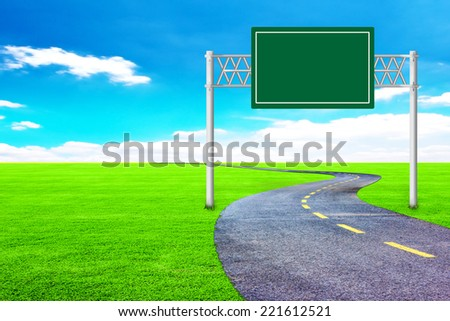 asphalt road with blank highway sign with green grass field representing the concept of journey to a focused destination resulting to success   - stock photo