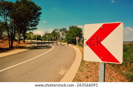 Asphalt road with chevron road signs - stock photo