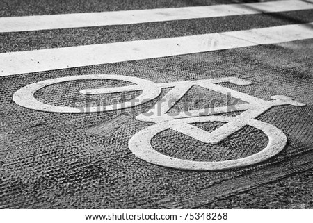 Asphalt road with cycle track and bike sign. - stock photo