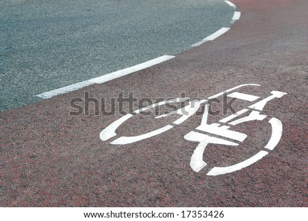 Asphalt road with cycle track and white bike logo