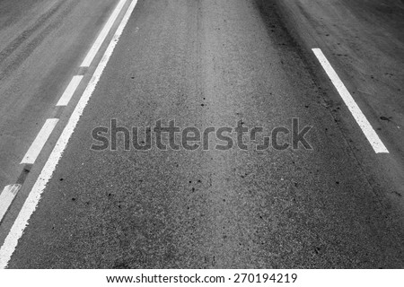 Asphalt road with dividing lines and tire tracks. Background photo with perspective effect - stock photo