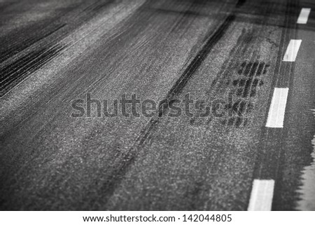 Asphalt road with marking lines and tire tracks. Close up photo with selective focus - stock photo