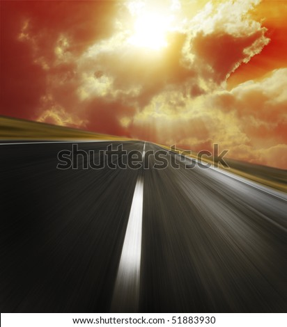 Asphalt road with red clouds and sunbeams - stock photo