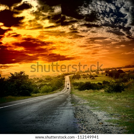 Asphalt road with red sunset sky - stock photo