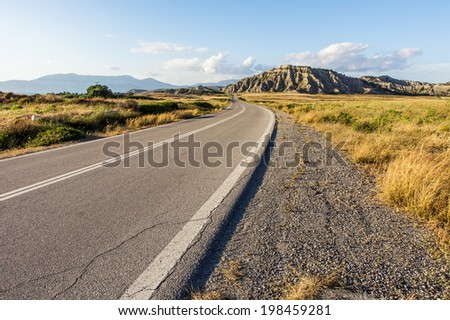 Asphalt Road with Separating Strips Going to the Mountains - stock photo