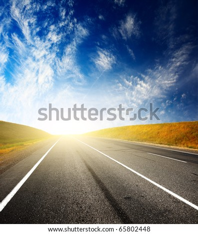 Asphalt road with sunlight on a horizon and blue sky with clouds