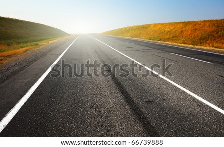 Asphalt road with sunlight on a horizon and clear blue sky - stock photo