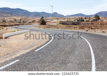 Asphalt road with white carriageway marking in mountain terrain of Africa - stock photo