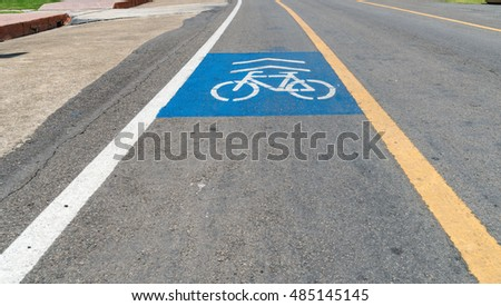 Asphalt road with yellow line and blue bicycle lane sign