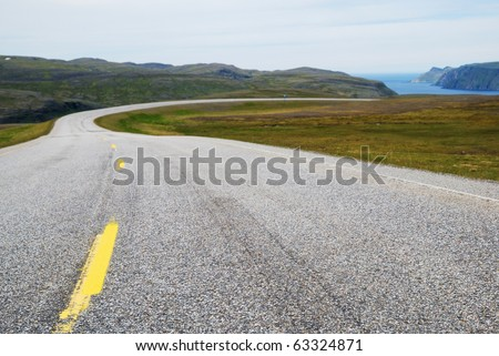 Asphalt road with yellow line is running to the blue fjord. Highway of Mageroya is photographed with diminishing perspective. - stock photo