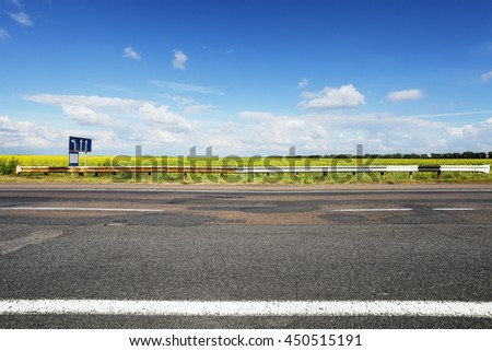 Asphalt rough road. Field of sun flowers on horizon. Summer landscape