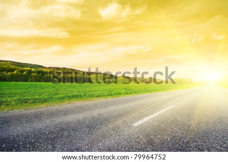 Asphalt rural road to sunrise - stock photo