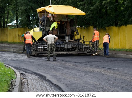 asphalt spreader is used to place the first layer of asphalt on a city street renewal project - stock photo