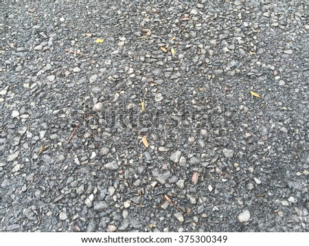 Asphalt surface of road with some small leaves - stock photo