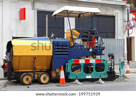 Asphalt surfacing and paving machine at street