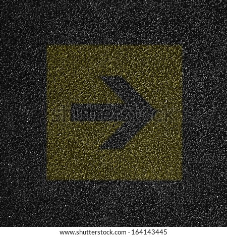 Asphalt texture or background with a yellow arrow on it - stock photo
