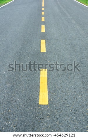 asphalt texture with yellow dashed line.