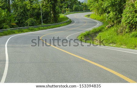 Asphalt winding curve road in nature - stock photo