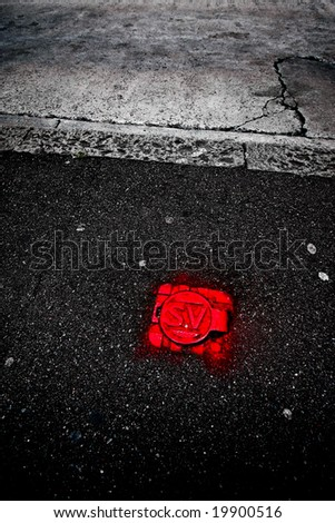 asphalt with distint red metal cover - stock photo