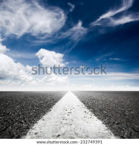 asphalted highway over blue sky background - stock photo