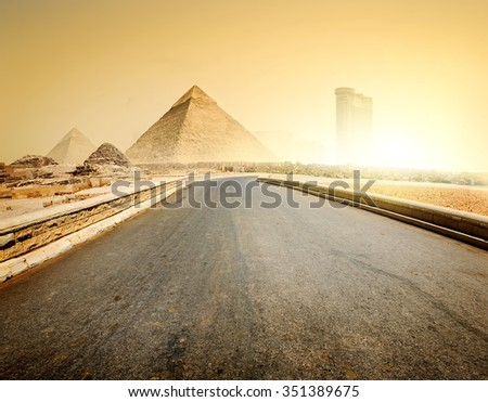 Asphalted road to piramids and modern buildings of Giza - stock photo