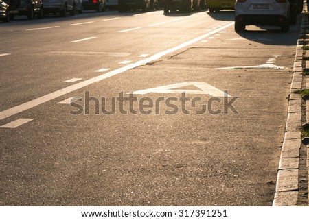 Asphalted traffic lanes against the sun during sunset. Public transport traffic lane. Glowing asphalt with road markings. - stock photo